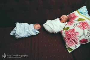Newborn twins swaddled and lying side-by-side on a sofa