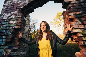 High school senior girl in yellow dress and black leather jacket standing in open brick doorway at Mason Mill Park