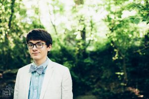 High school senior boy in woods with glasses and bow tie