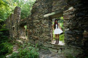 High school senior girl in white dress standing in Sope Creek paper mill ruins