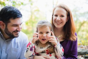 Goofy little girl making faces while her parents laugh