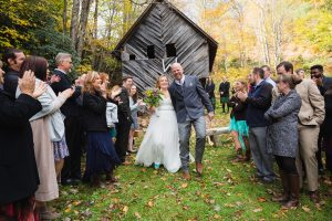Bride + Groom exiting ceremony with cheering guests in front of old Ashevill barn in the mountains