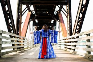 High school senior wearing purple and red kimono with arms outstretched in the middle of a bridge