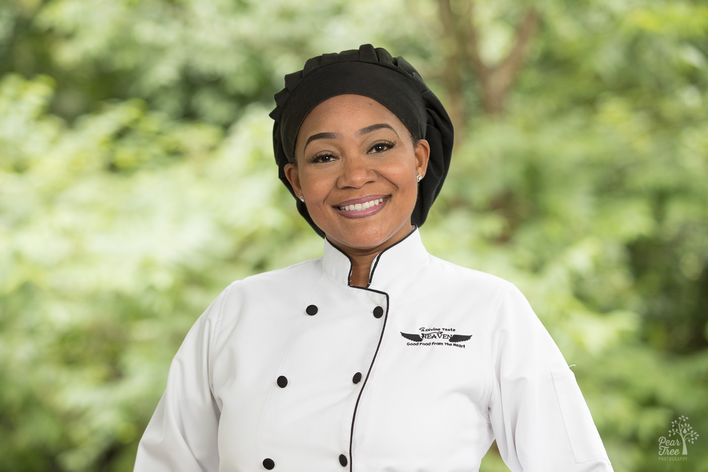 Headshot of chef Shantel Dean in white chef coat and black chef hat with Divine Taste of Heaven