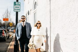 Smiling pregnant bride walking through downtown Marietta square with her husband and both wearing sunglasses