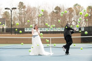 Bride + Groom on tennis court laughing as dozens of tennis balls come at them