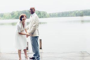 Happy married couple standing and laughing on Lake Acworth dock