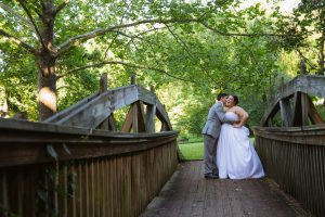 Bride + Groom embracing on Mountain Park bridge in Roswell