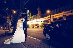 Bride + Groom kissing with Atlanta Fox Theater in background and as car stops to watch