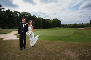Bride kicking her heel up and smiling in sunglasses while standing next to her husband in front of Stone Mountain golf course