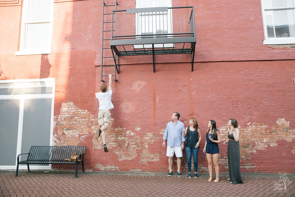 Family looking at the oldest jumping up a wall to grab a fire escape in downtown Canton