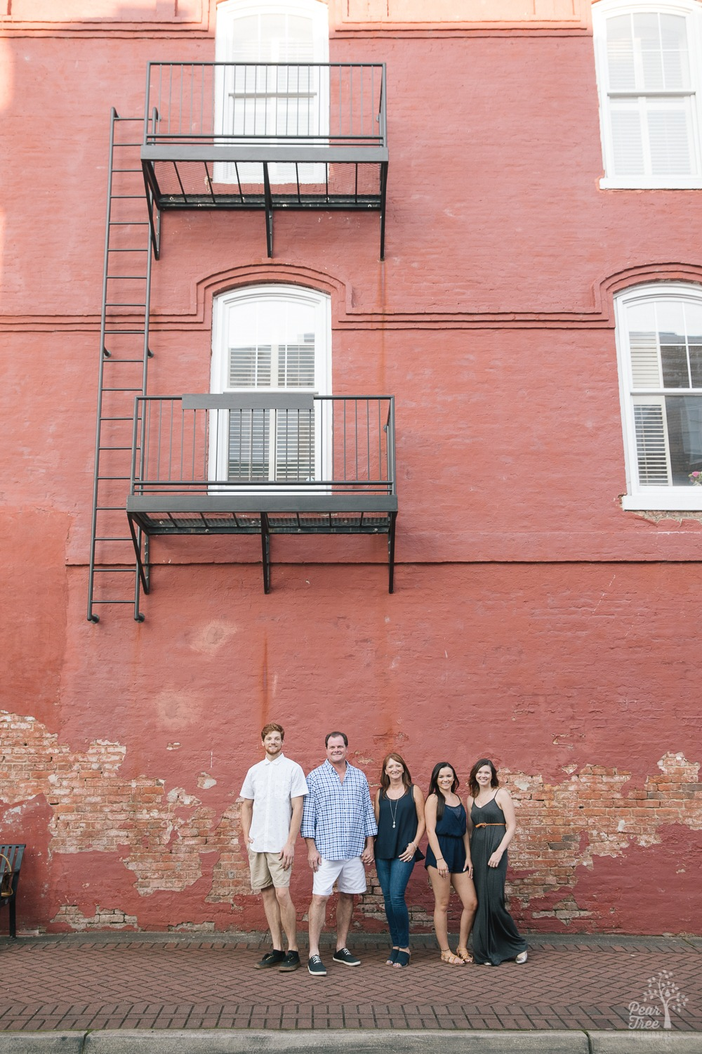 Happy family of two parents and three grown children standing together in downtown Canton under a fire escape in front of an old brick wall.