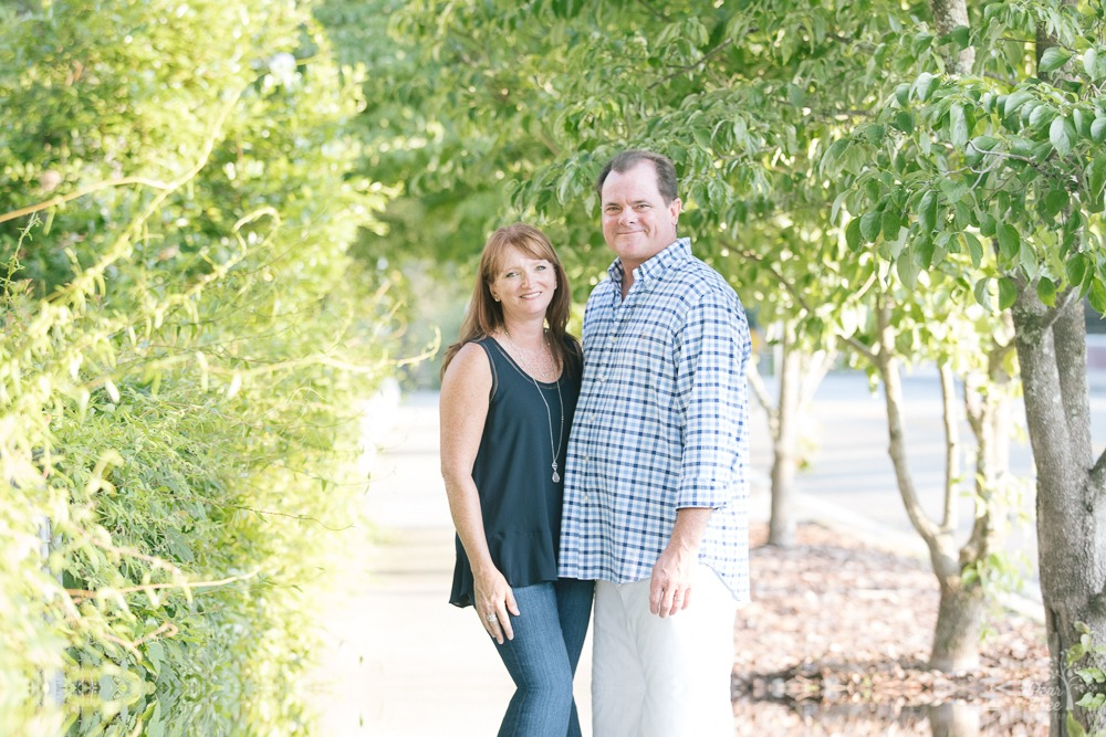 Jenna and Arnie Seyden standing close and smiling on a sidewalk surrounded by green crepe myrtles.