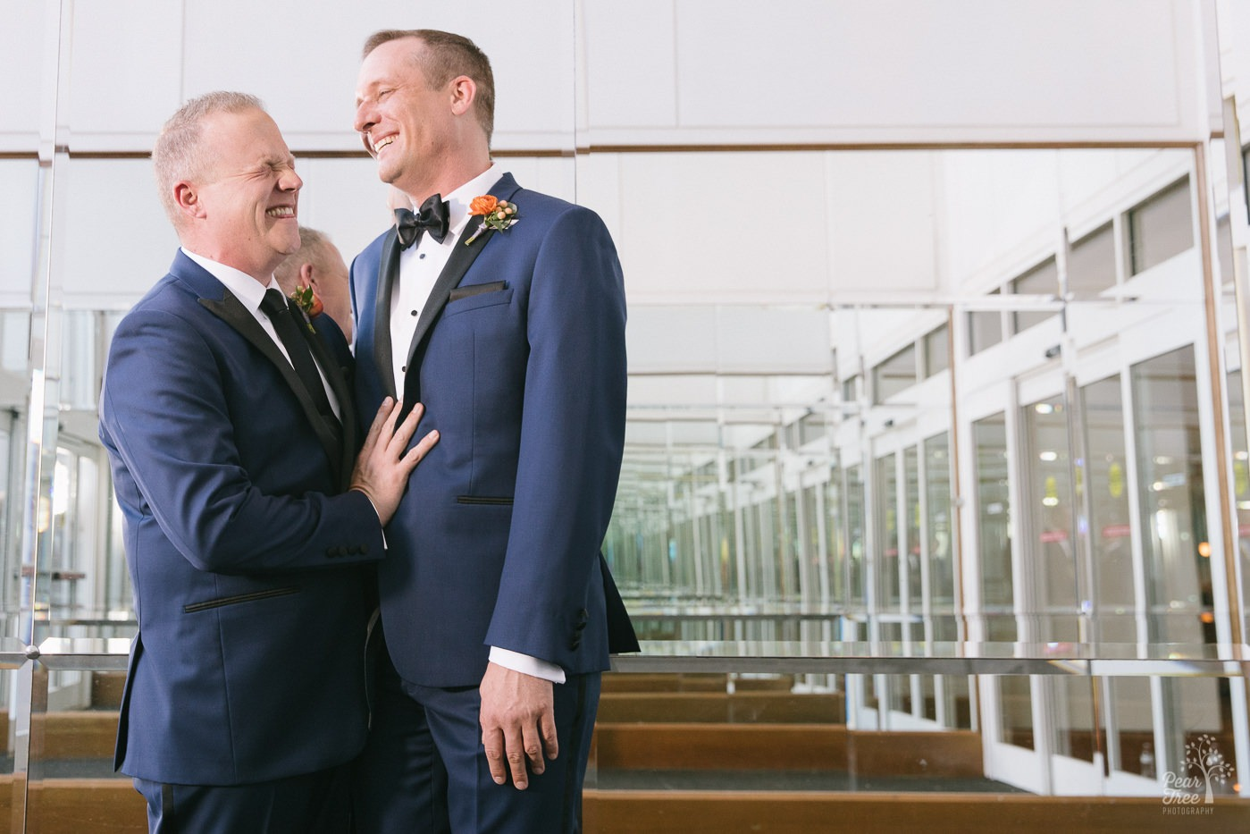 Two grooms laughing inside Renaissance Concourse Atlanta lobby of mirrors.