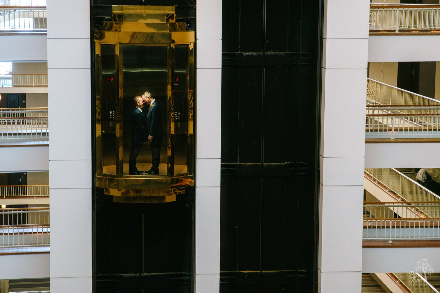 Two grooms facing each other, holding hands, and touching foreheads inside Renaissance Concourse Atlanta Airport Hotel elevator.
