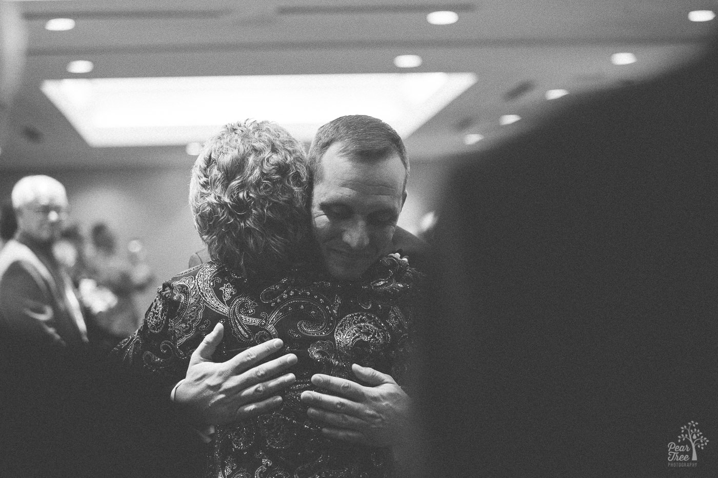 Groom hugging his mom after she walked him down the aisle for his marriage ceremony.