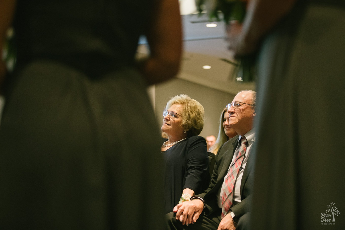 Groom's parents holding hands and smiling as they watch their son get married inside Renaissance Concourse Atlanta Airport Hotel.