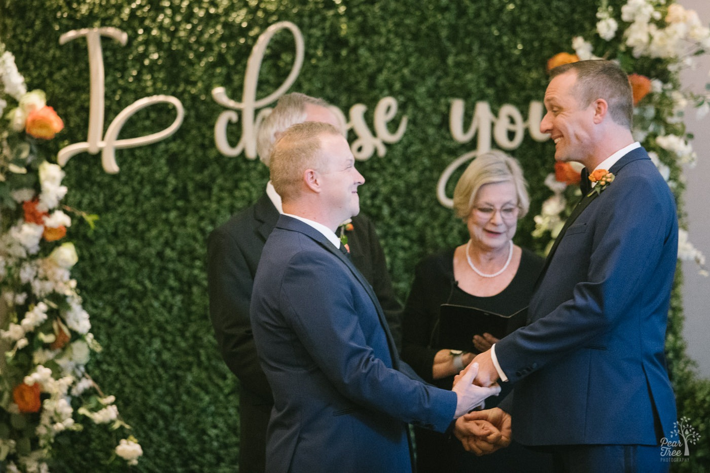 Grooms smiling in excitement as they're told they are officially married and can kiss each other.