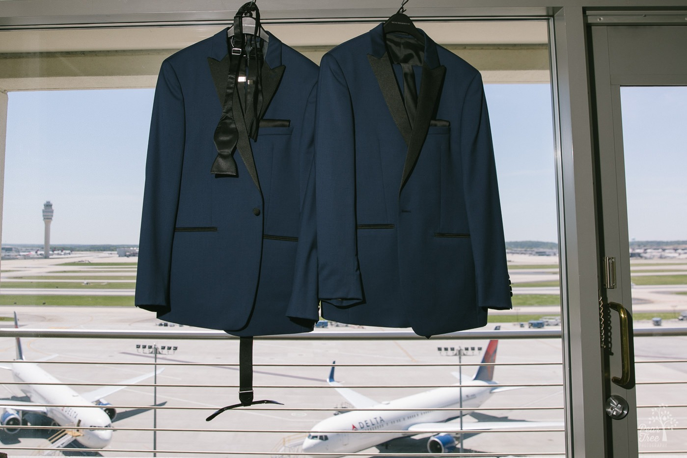 Two tuxes hanging in Atlanta Renaissance Concourse penthouse window overlooking Delta jets at Hartsfield-Jackson International Airport.