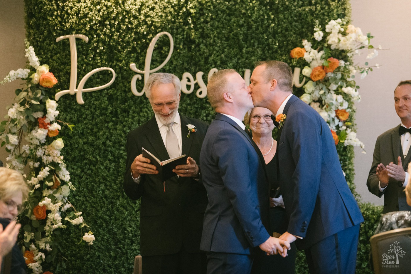 Grooms kissing after getting married inside Renaissance Concourse Atlanta Airport Hotel.