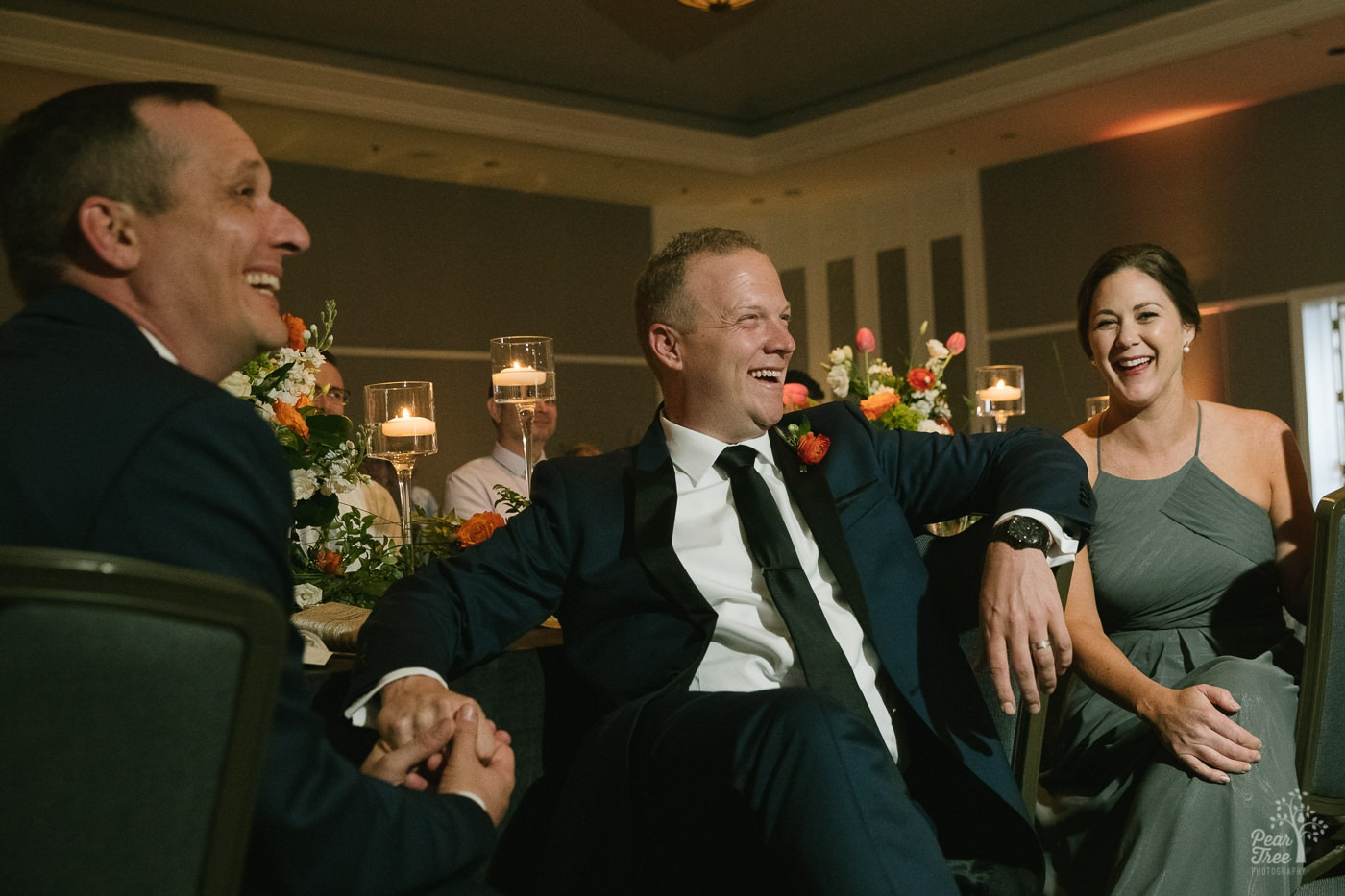Two grooms and one maid of honor laughing during toasts at reception inside Renaissance Concourse Atlanta Airport Hotel.