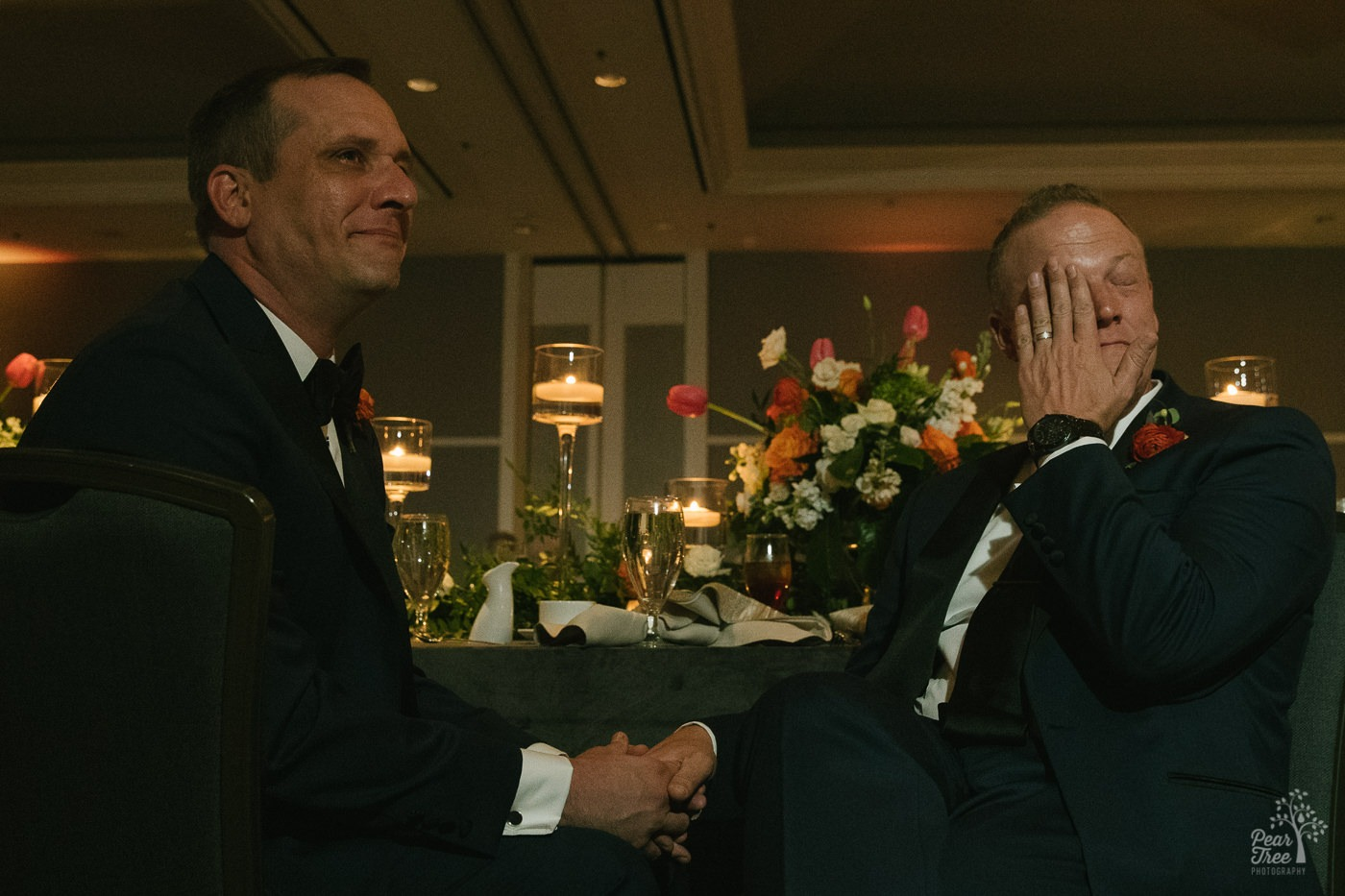 Grooms holding hands and one wiping away tears during wedding toasts.