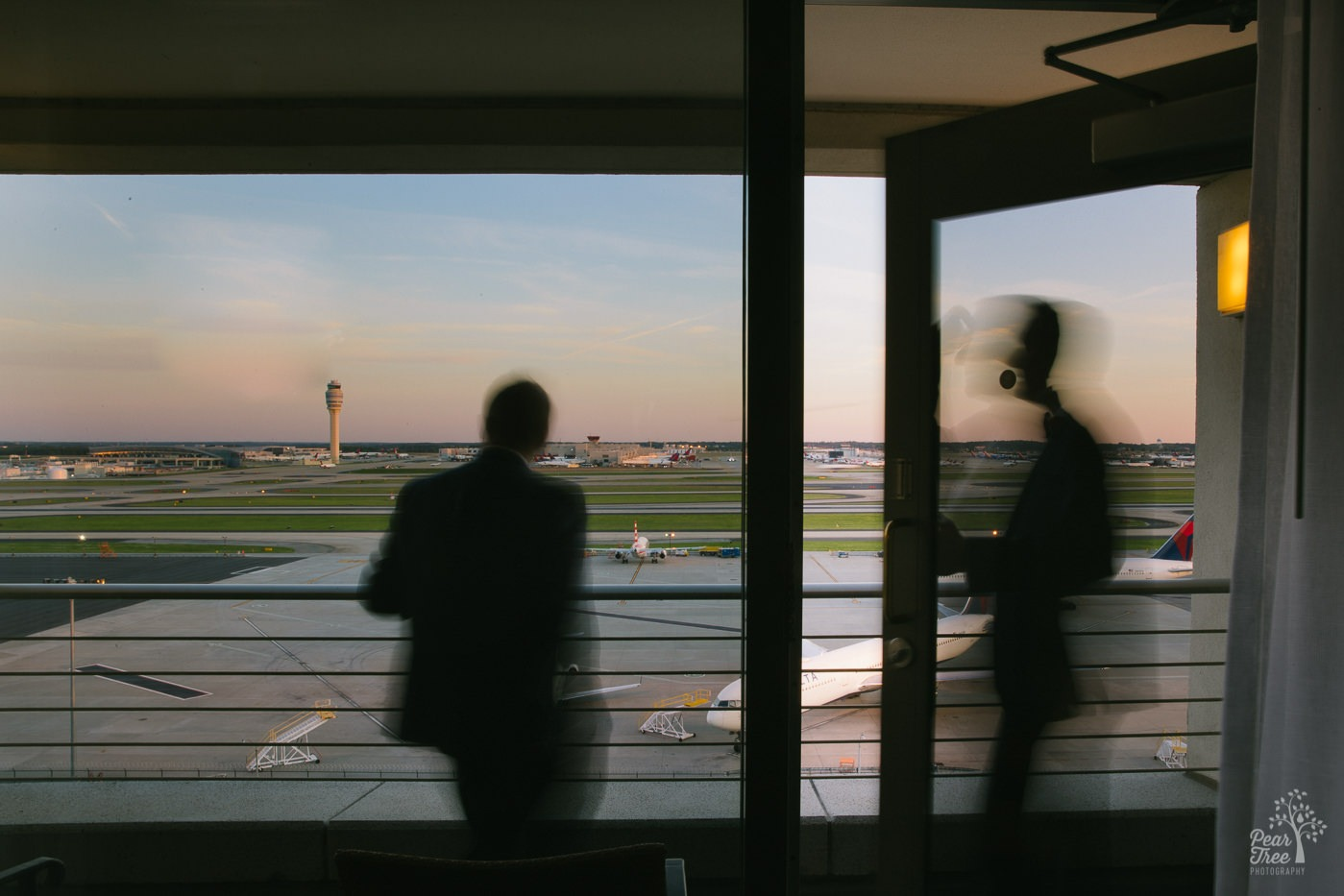 Silhouettes of two grooms on Renaissance Concourse Atlanta Airport Hotel penthouse balcony overlooking Hartsfield runways with Delta jets parked on the tarmac.