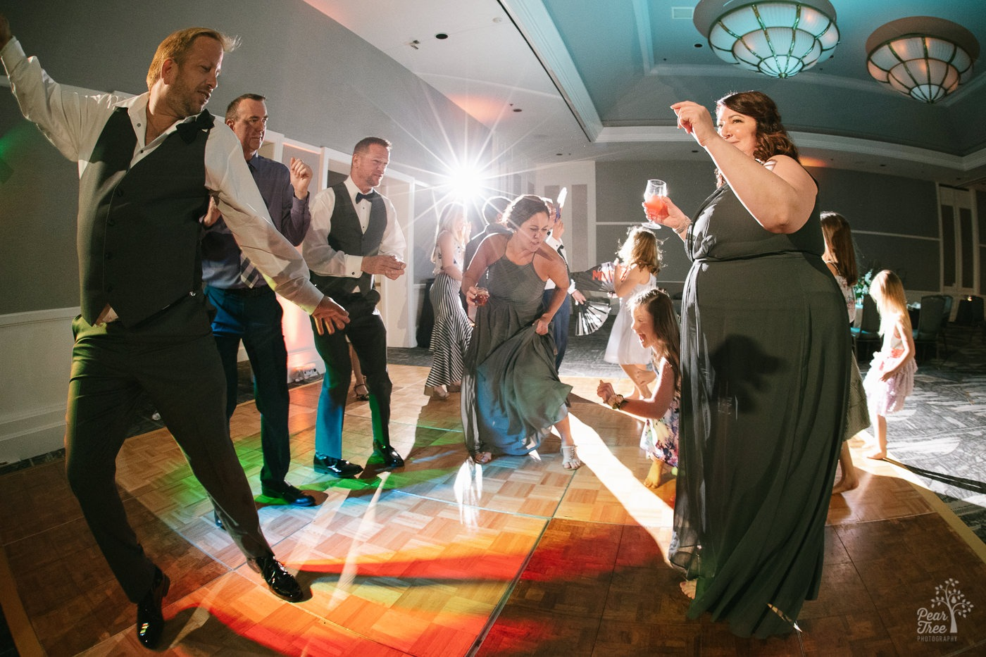 Groomsmen dancing with Matron of Honor, Maid of Honor, and children on dance floor.