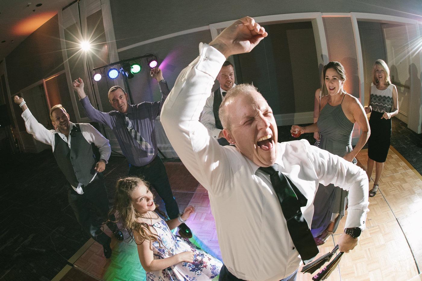Groom dancing and laughing on dance floor.