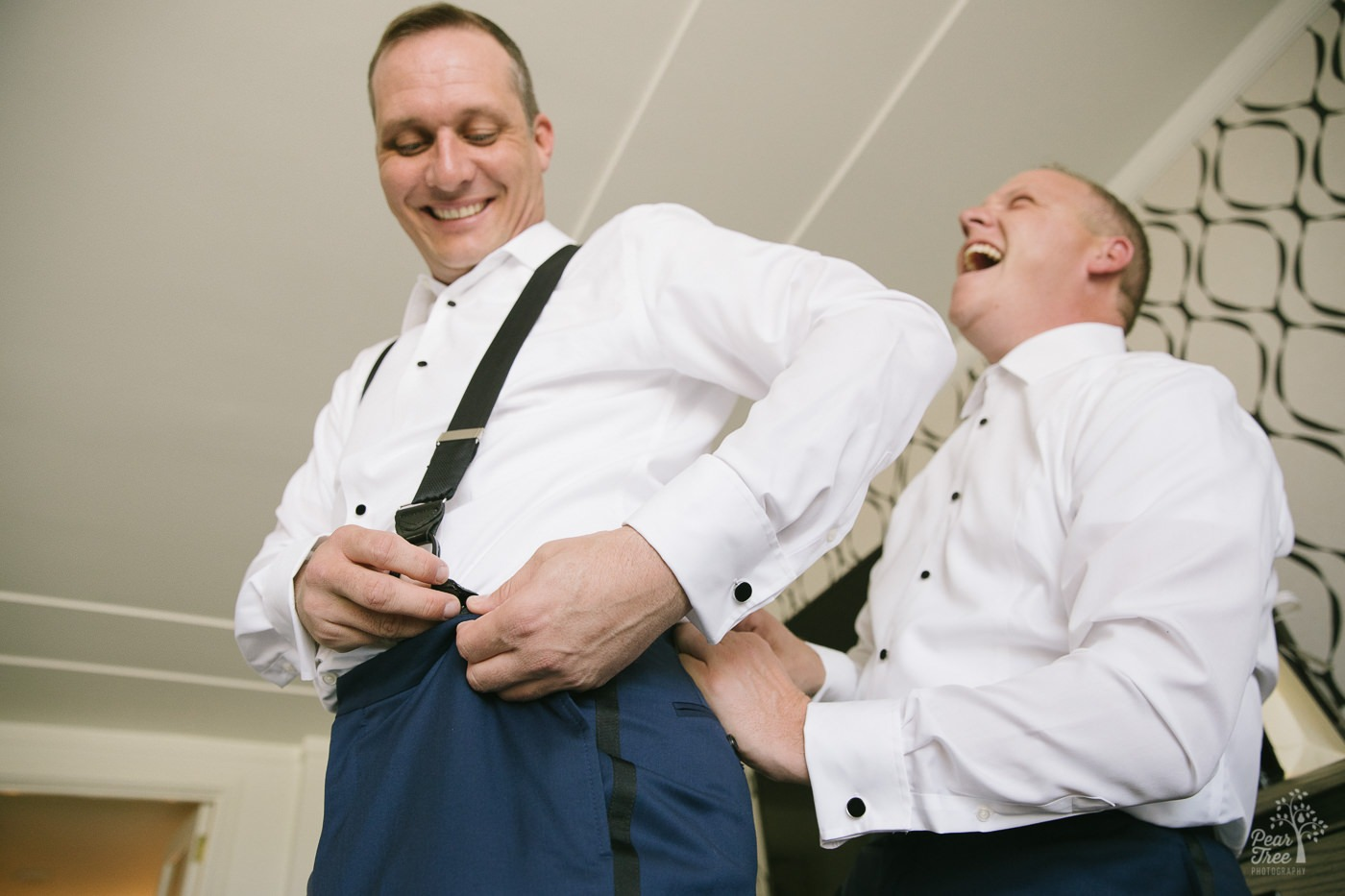 Two grooms laughing and helping fasten suspenders.