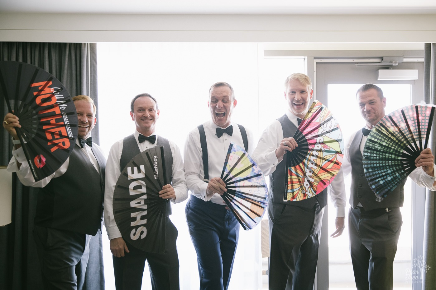 Groom with four groomsmen showing off their large, fancy fans.
