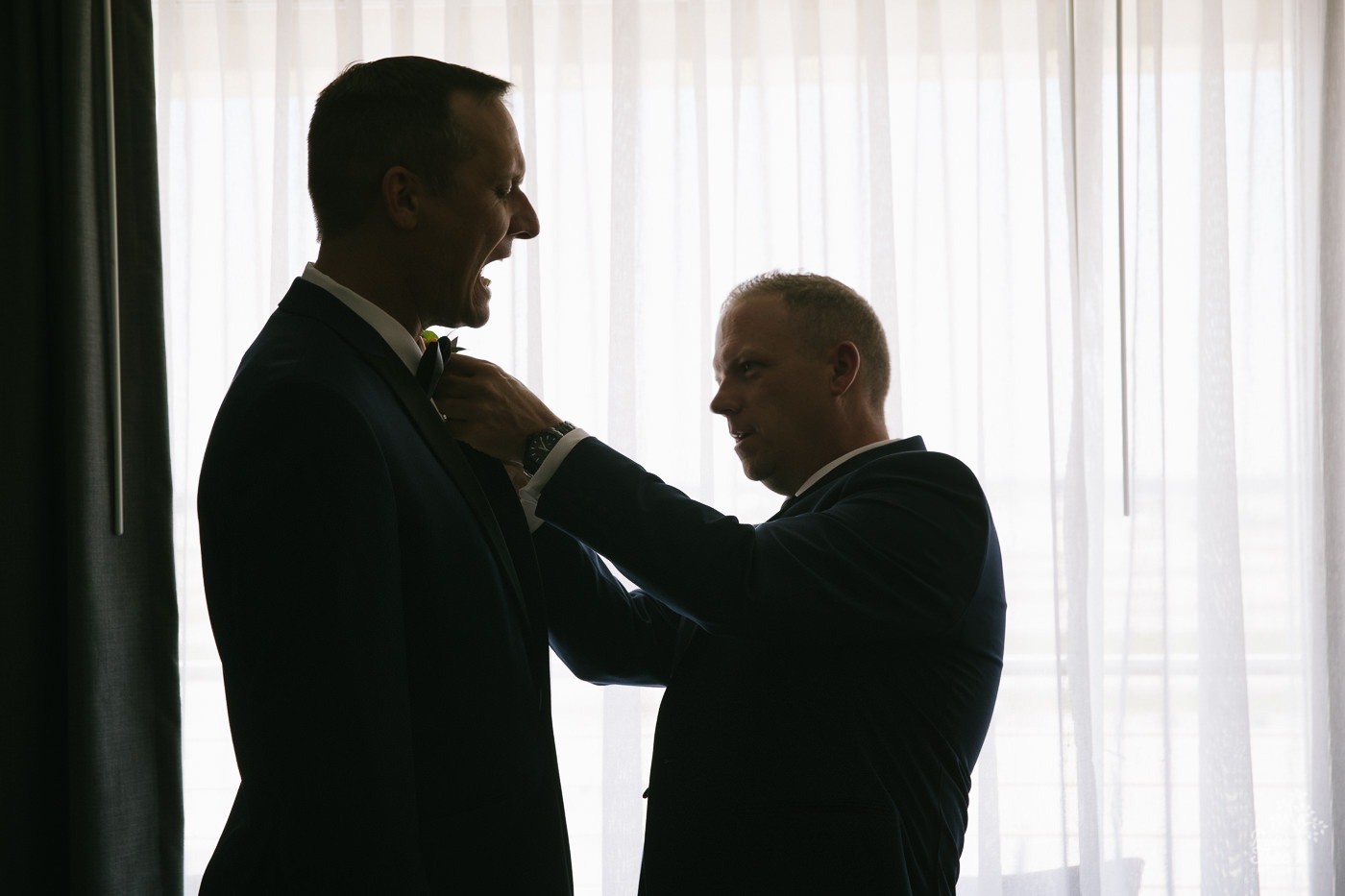 One groom pinning a boutonierre on his love's lapel and accidentally poking him.