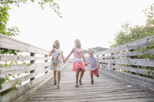 Three Algerian children running and laughing on Lake Acworth boardwalk