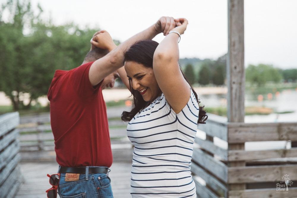 Smiling Algerian-American couple dancing on Lake Acworth boardwalk