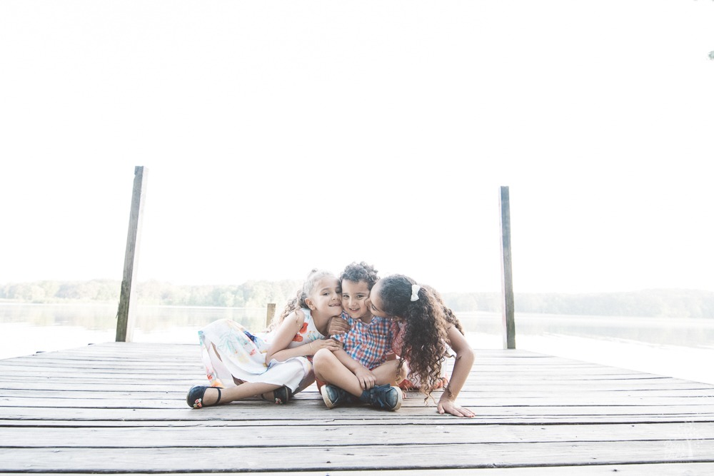 Two big sisters hugging and kissing their little brother at Lake Acworth.