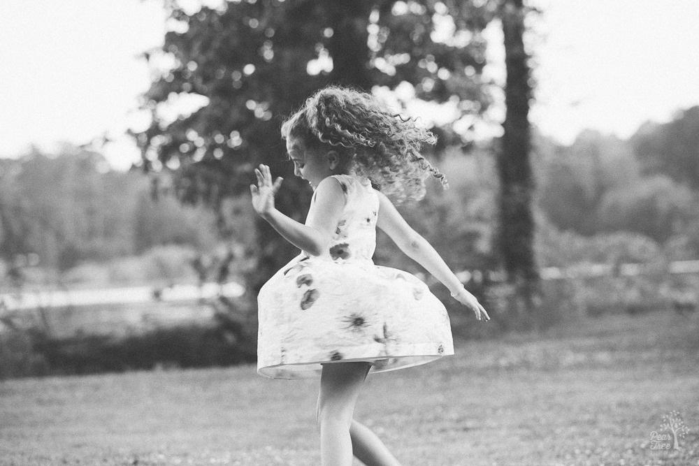 Little girl twirling and making her dress fly out.