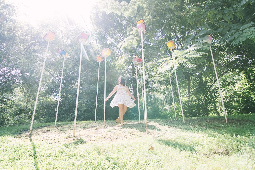 High school girl twirling in between bird houses as the sun makes her spinning dress shine and glow.