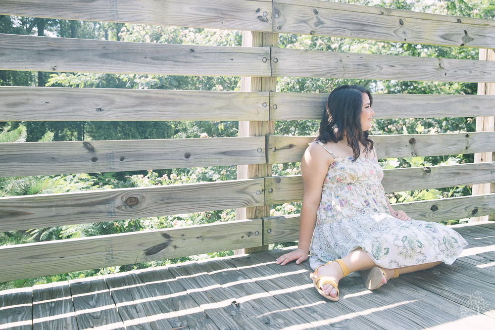 High school girl sitting on boardwalk in floral sundress.