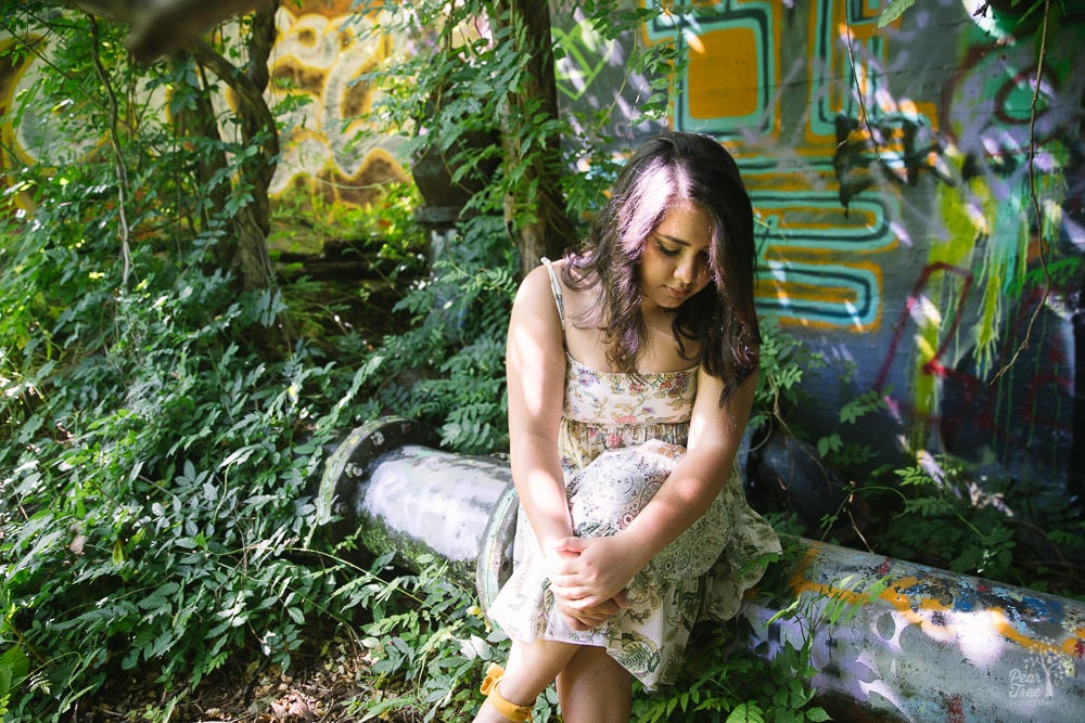 High school girl sitting on Decatur Water Works pipeline surrounded by overgrown foliage and graffiti in the background.