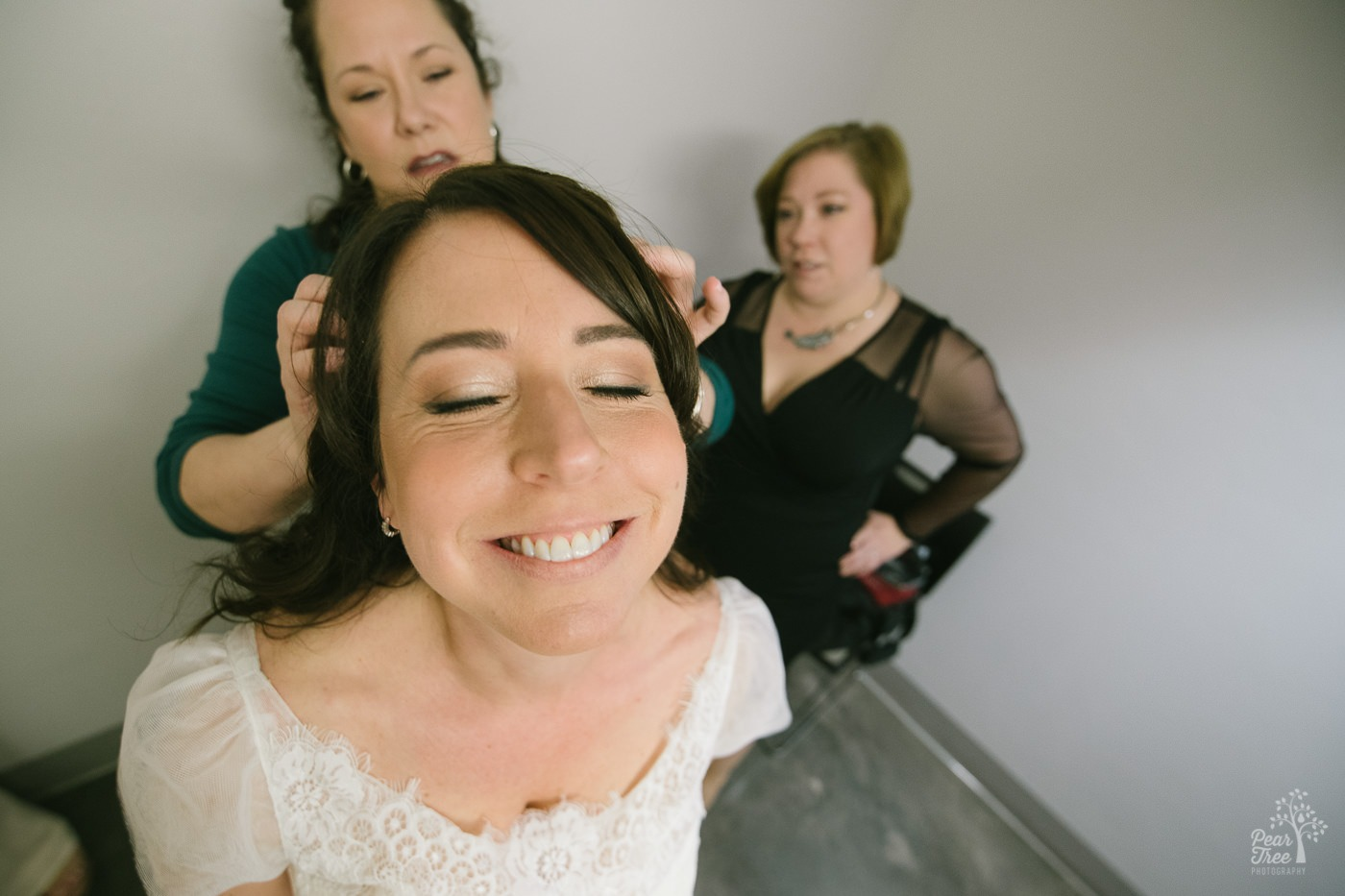 Bride smiling while her best friend is adjusting her hair.