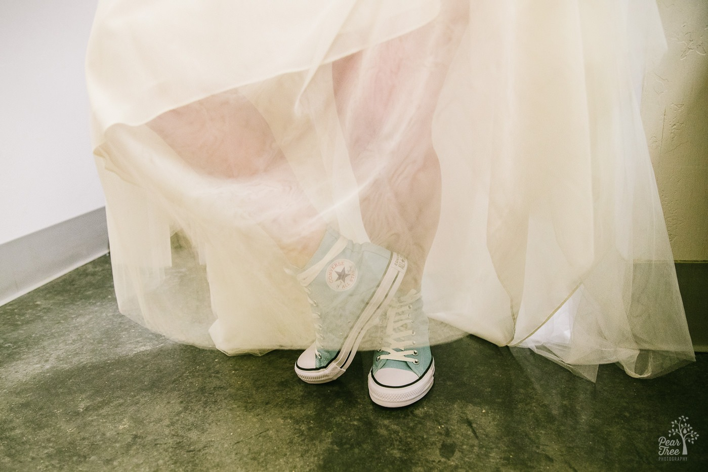 Turquoise high top Converse wearing bride.