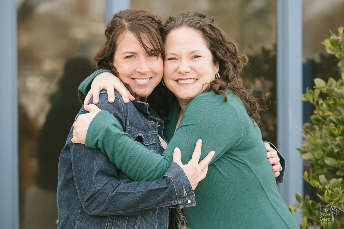 Two brunette best friends hugging each other and smiling.