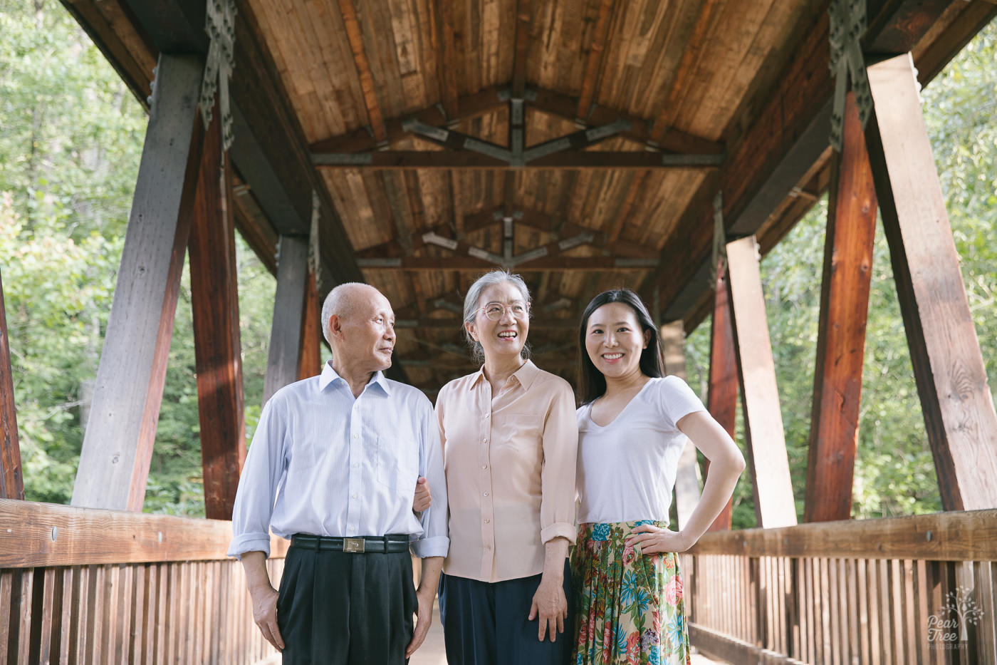 Proud Chinese parents standing in covered bridge at Roswell Mill with their adult daughter.