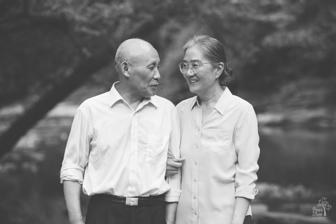 Smiling Chinese woman holding her husband close by his arm.