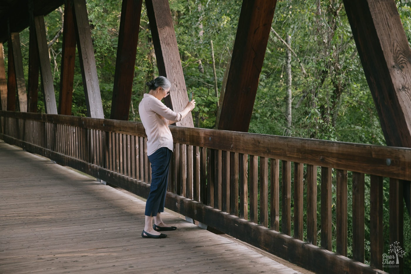 Chinese woman using her cell phone to take pictures of Vickery Creek from the covered bridge.