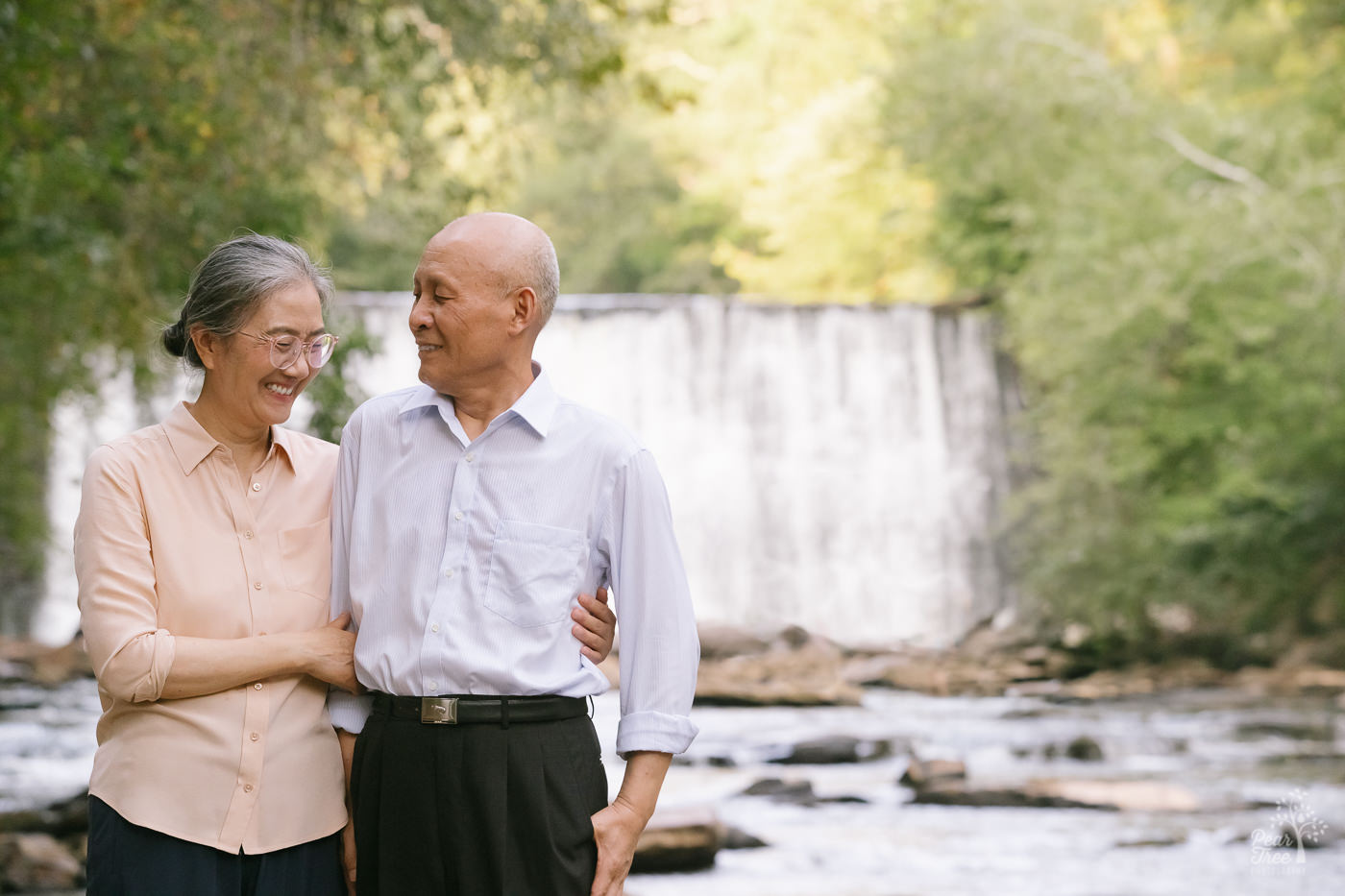 Laughing Chinese couple standing in front of waterfall at Vickery Creek.