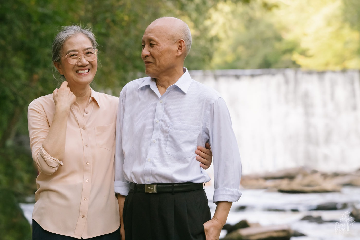 Smiling Chinese woman holding her husband around the waist in front of waterfall at Roswell Mill.