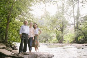Chinese parents standing with their adult daughter at Vickery Creek near Roswell Mill
