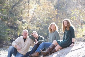 Family of four with two teenagers sitting on the shoals at Sope Creek in the morning sun