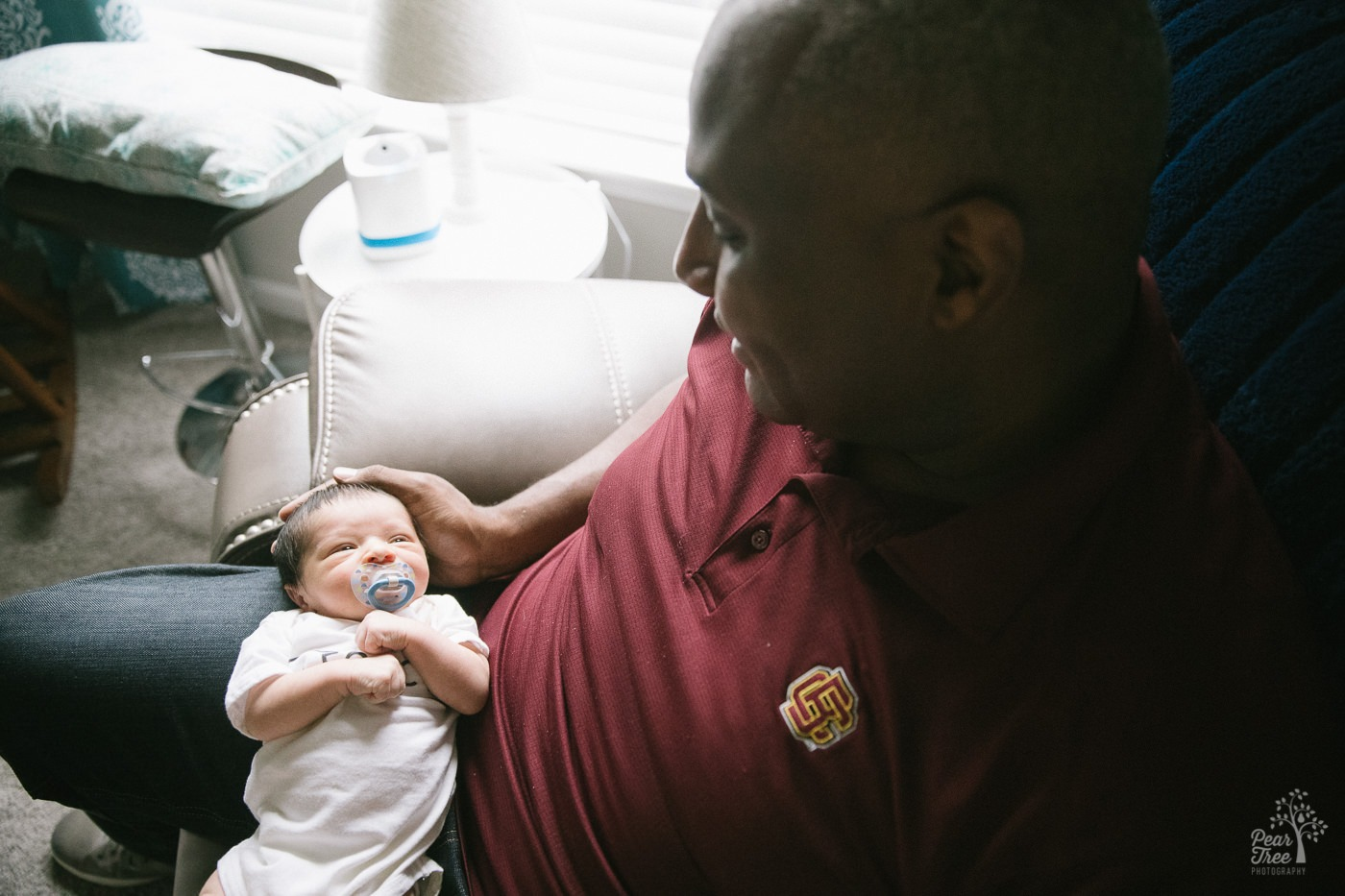 Dad holding five day old newborn son in his lap.